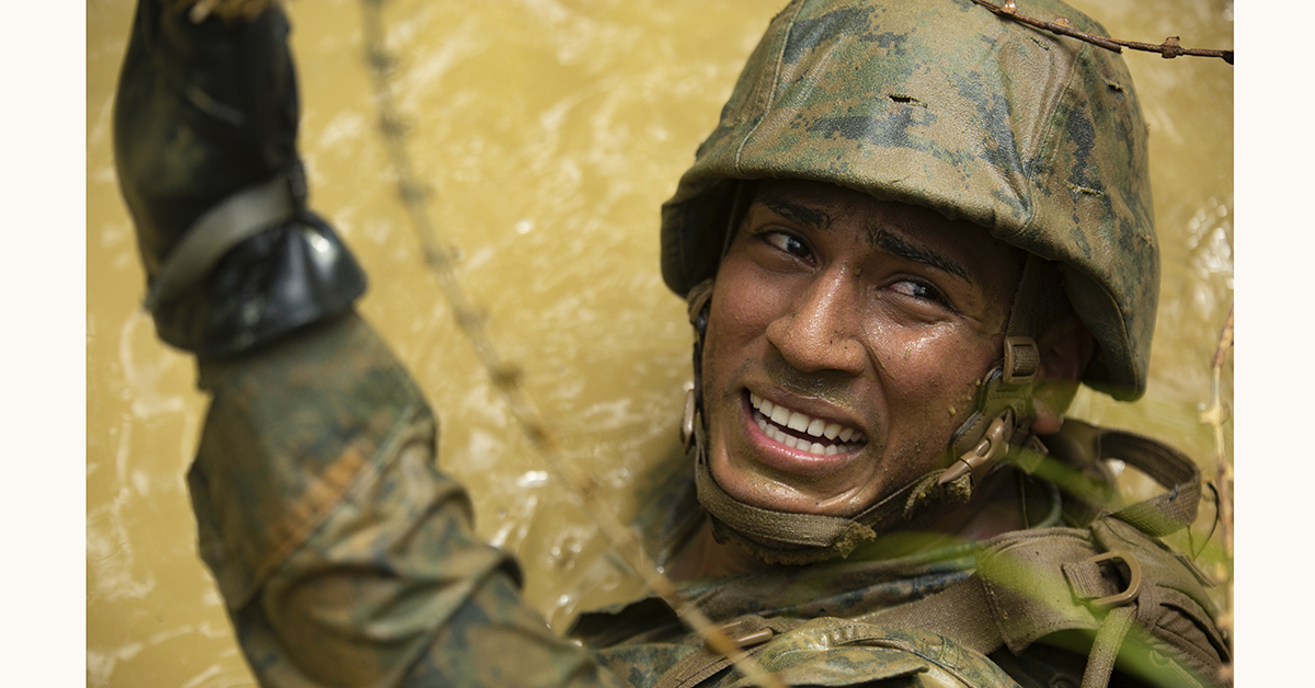 Seaman Cesar Ramirez-Fajardo maneuvers through razor wire at the Jungle Warfare Training Center, Camp Gonsalves, Okinawa, Japan. Ramirez-Fajardo, from Orlando, Florida, is a field medical service technician with 3rd Law Enforcement Battalion, III Marine Expeditionary Force Information Group. While going through certain obstacles, Marines and Sailors were required to move through murky water, confined spaces and razor wire. (Pfc. Andrew R. Bray/Marine Corps)