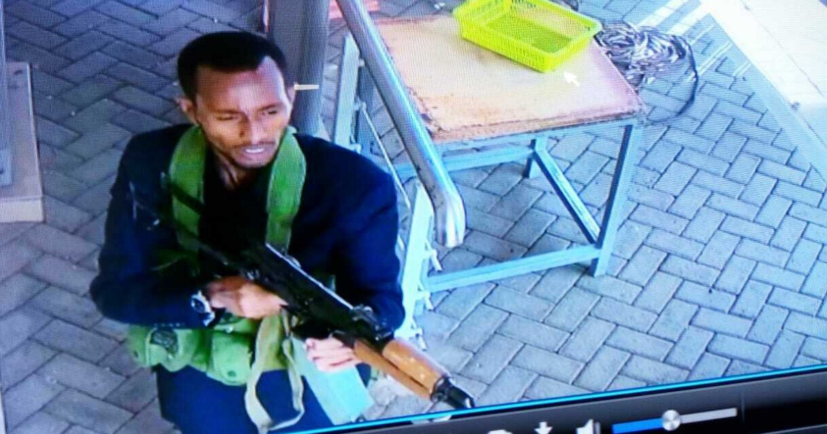 In this image taken from security camera footage Jan. 15, an armed militant walks in the compound of a hotel, in Nairobi, Kenya. Extremists launched an attack on a luxury hotel in Kenya's capital, sending people fleeing in panic as explosions and heavy gunfire reverberate through the neighborhood. Al-Shabab -- the Somalia-based extremist group -- claimed responsibility. (security camera footage via AP)