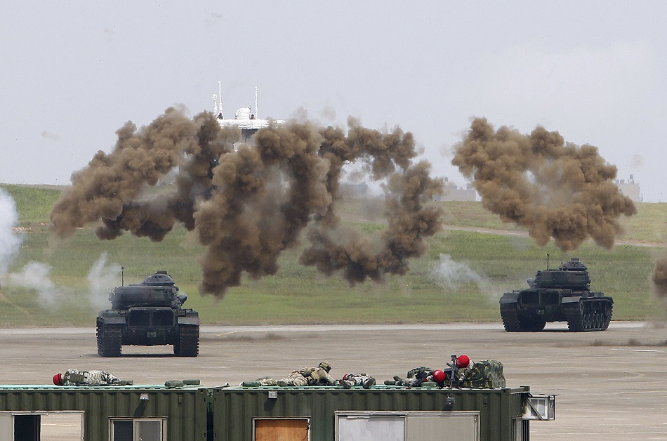 Tanks perform drills amid heavy smoke during the Han Kuang exercises at an air base in Taiwan. Taiwan's war games are intended to display the military's willingness and ability to fight off an invasion from China. (Chiang Ying-ying/AP)