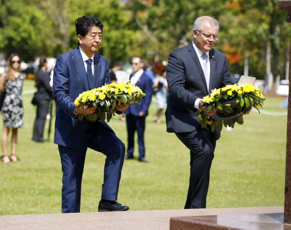 Japanese Prime Minister Shinzo Abe, left, lays a wreath along with Australian Prime Minister Scott Morrison at the Cenotaph War Memorial in Darwin, Australia on Friday. (Glenn Campbell/Pool Photo via AP)