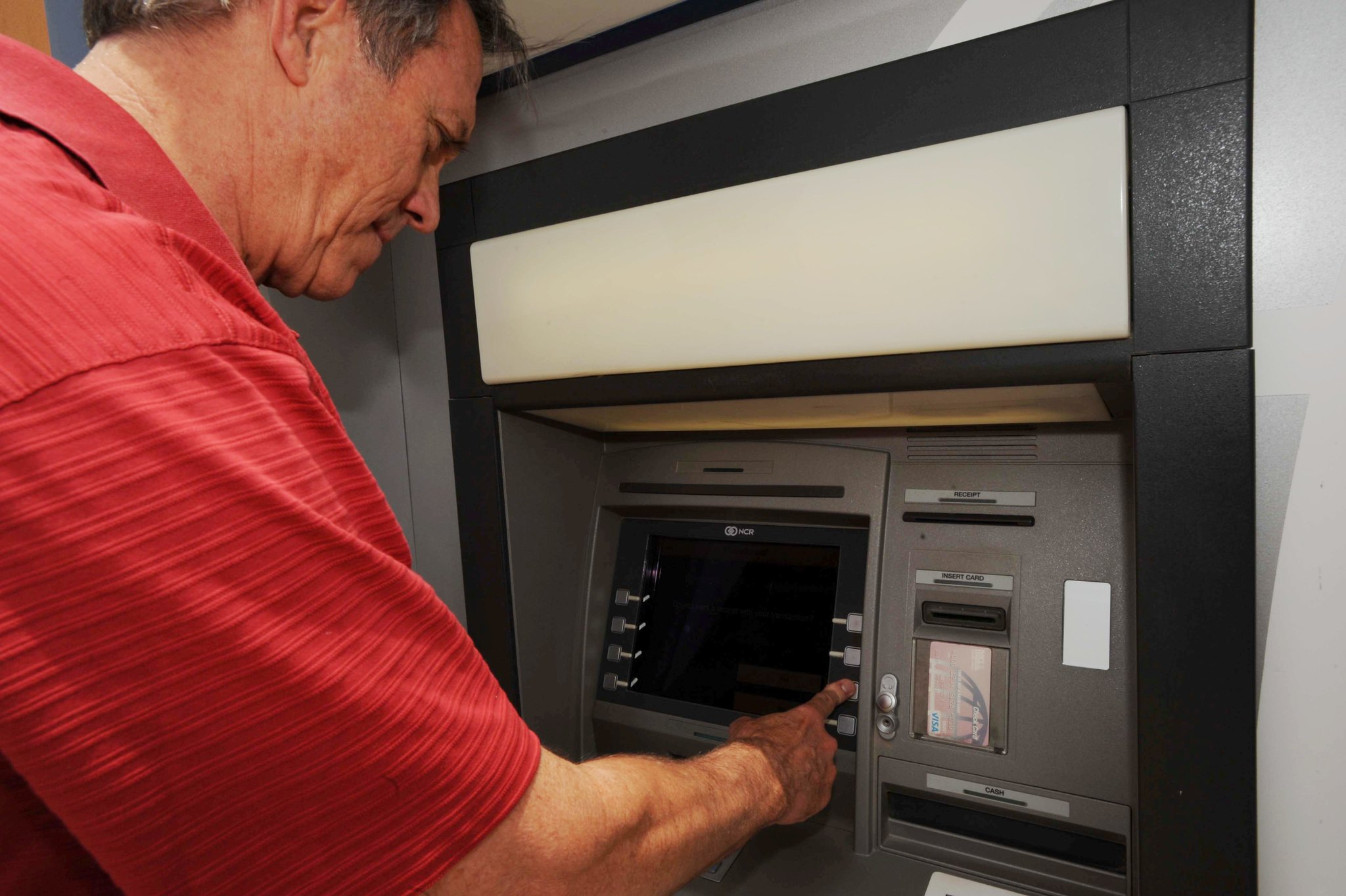 Retired Navy Vice Adm. Cutler Dawson, president and CEO of Navy Federal Credit Union, uses an NFCU ATM at Camp Lemonnier, Djibouti, May 22, 2010. (Staff Sgt. Robert Barnett/Air Force)
