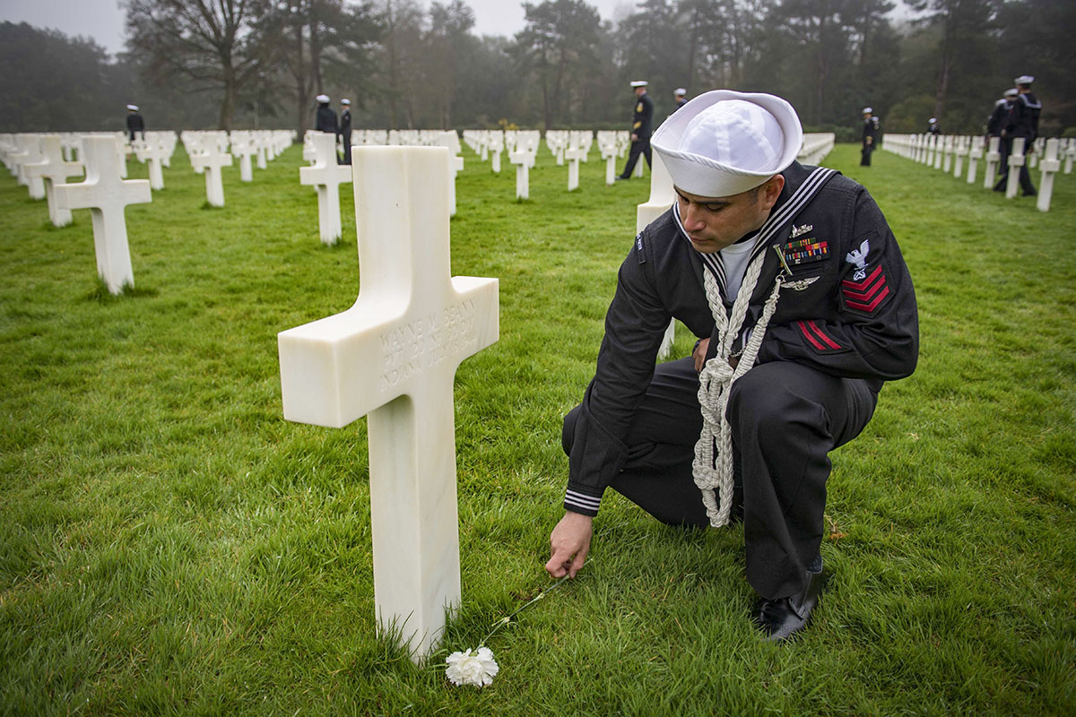 180408-N-JI086-362 SAINT LAURENT SUR MER, France (April 8, 2018) Boatswain's Mate 1st Class Derrick Manzano, assigned to the Arleigh Burke-class guided-missile destroyer USS Porter (DDG 78), places a rose at a headstone of U.S. Army Pvt. Wayne M. Beann at the Normandy American Cemetery and Memorial, April 8, 2018. Porter, forward-deployed to Rota, Spain, is on its fifth patrol in the U.S. 6th Fleet area of operations in support of U.S. national security interests in Europe. (MC3 Ford Williams/Navy)