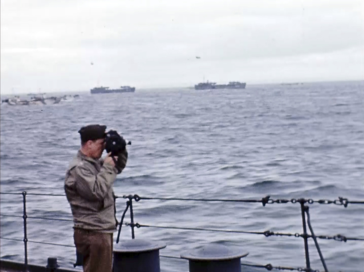 Hollywood director George Stevens looks through a camera on a ship off the coast of France on D-Day, June 6, 1944. Stevens was assigned to to head up the combat motion-picture coverage, but he was also using 16-millimeter color film for himself of the same events, creating a kind of personal video journal of his experiences. (War Footage From the George Stevens Collection at the Library of Congress via AP)