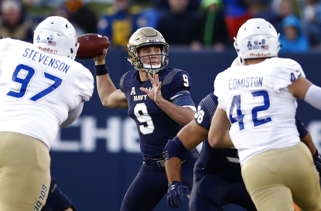Navy's Zach Abey, center, throws as he is pressured by Tulsa defensive tackle Tyarise Stevenson, left, and linebacker Cooper Edmiston on Saturday in Annapolis, Md. (Patrick Semansky/AP)