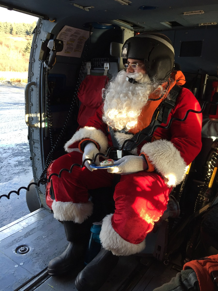 Santa Claus waits in a Coast Guard Air Station Kodiak MH-60 Jayhawk helicopter to take off to take him to the next remote Kodiak Island, Alaska, village, Dec. 5, 2017. (Petty Officer 1st Class Charly Hengen/Coast Guard)