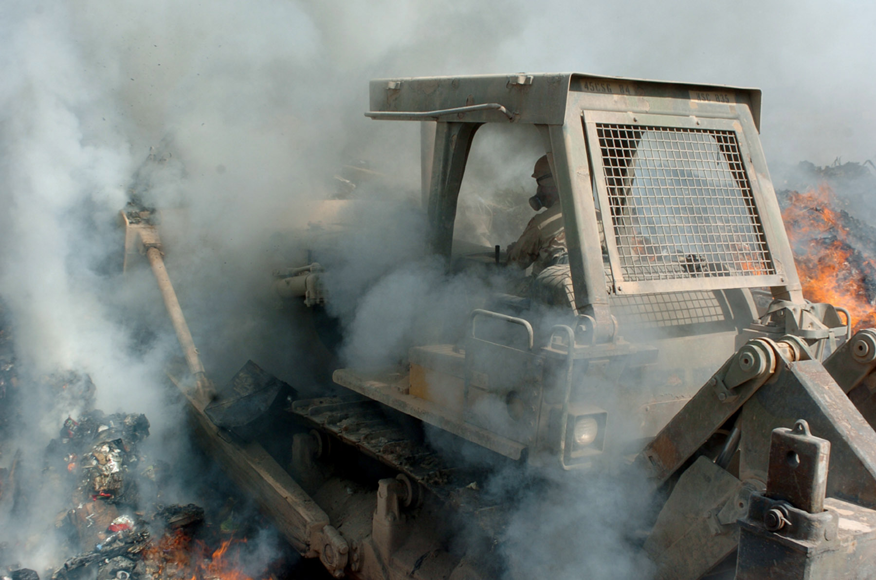 In this file photo, Army Sgt. Richard Ganske, 84th Combat Engineer Battalion, pushes the bulldozer deep into the flames of the burn pit to keep burnable items constantly ablaze at Logistics Support Area Anaconda, Balad, Iraq.