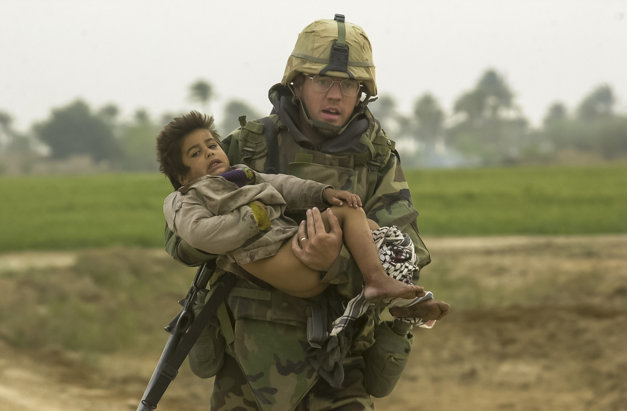 PFC Joseph DeWitt, 26, from Suffock County, Ny, runs while carrying a young Iraqi boy who was injured during a heavy batle between the U.S. Army's 7th Cavalry Regiment and Iraqi forces near the village of Al Faysaliyah, Iraq. The Cavalry spent the entire night fighting through the areas and within the city of Al Faysaliyah. The U.S. took no casualties while the Iraqis took estimated 150 casualties inflicted by the Cavalry on March 25, 2003. (Warren Zinn/Army Times)