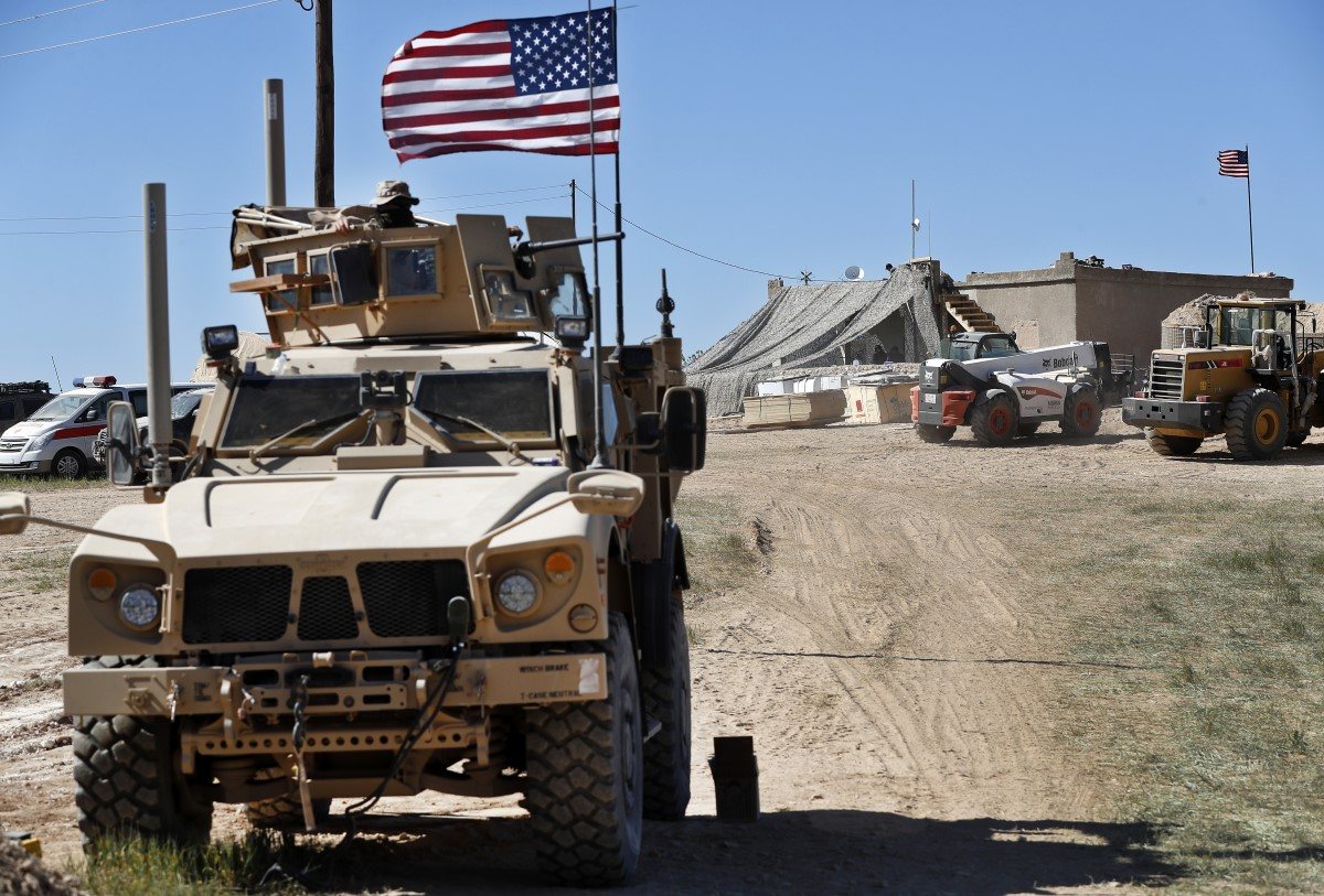 In April, a U.S. soldier sits on an armored vehicle at a newly installed position near the front line between the U.S-backed Syrian Manbij Military Council and the Turkish-backed fighters, in Manbij, Syria. (Hussein Malla/AP)