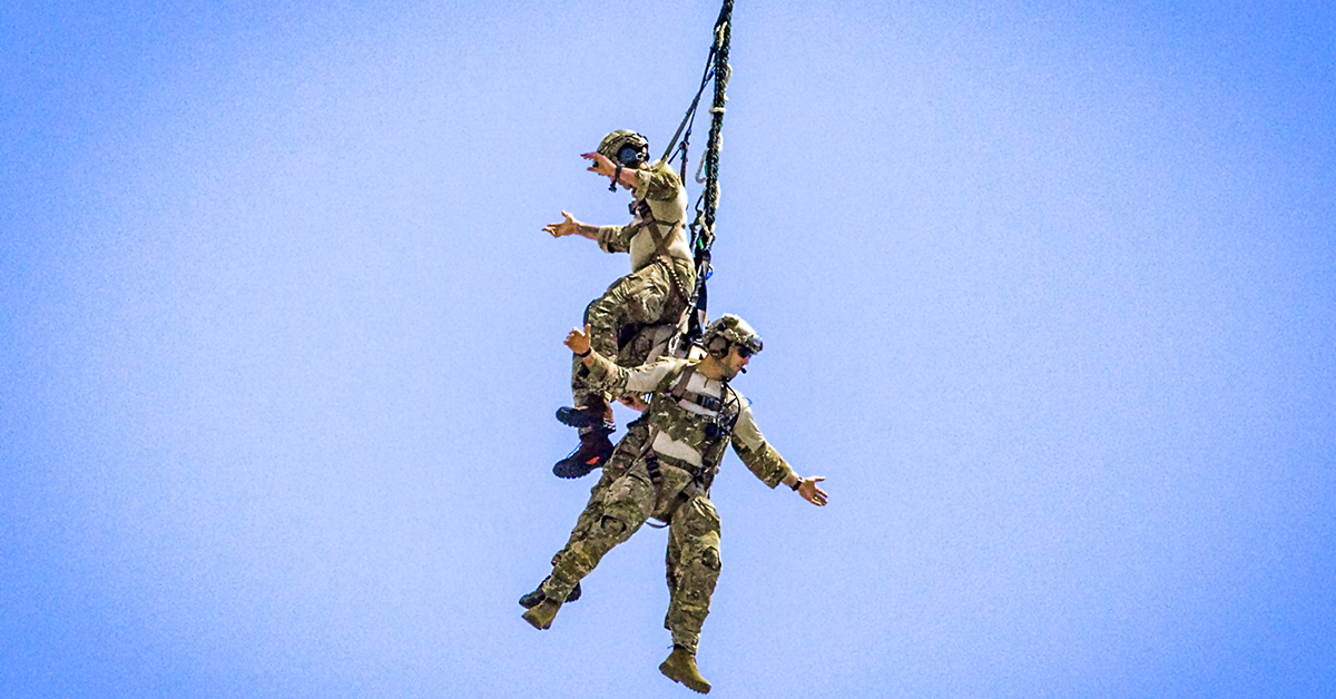 Tactical air control party Airmen with the 227th Air Support Operations Squadron, New Jersey Air National Guard, demonstrate a special extraction system while hanging from a UH-60L Black Hawk helicopter assigned to the 1st Assault Helicopter Battalion, New Jersey Army National Guard, during the 2018 Atlantic City International Airshow at Atlantic City, New Jersey, Aug. 22, 2018. (Mark C. Olsen/New Jersey National Guard)