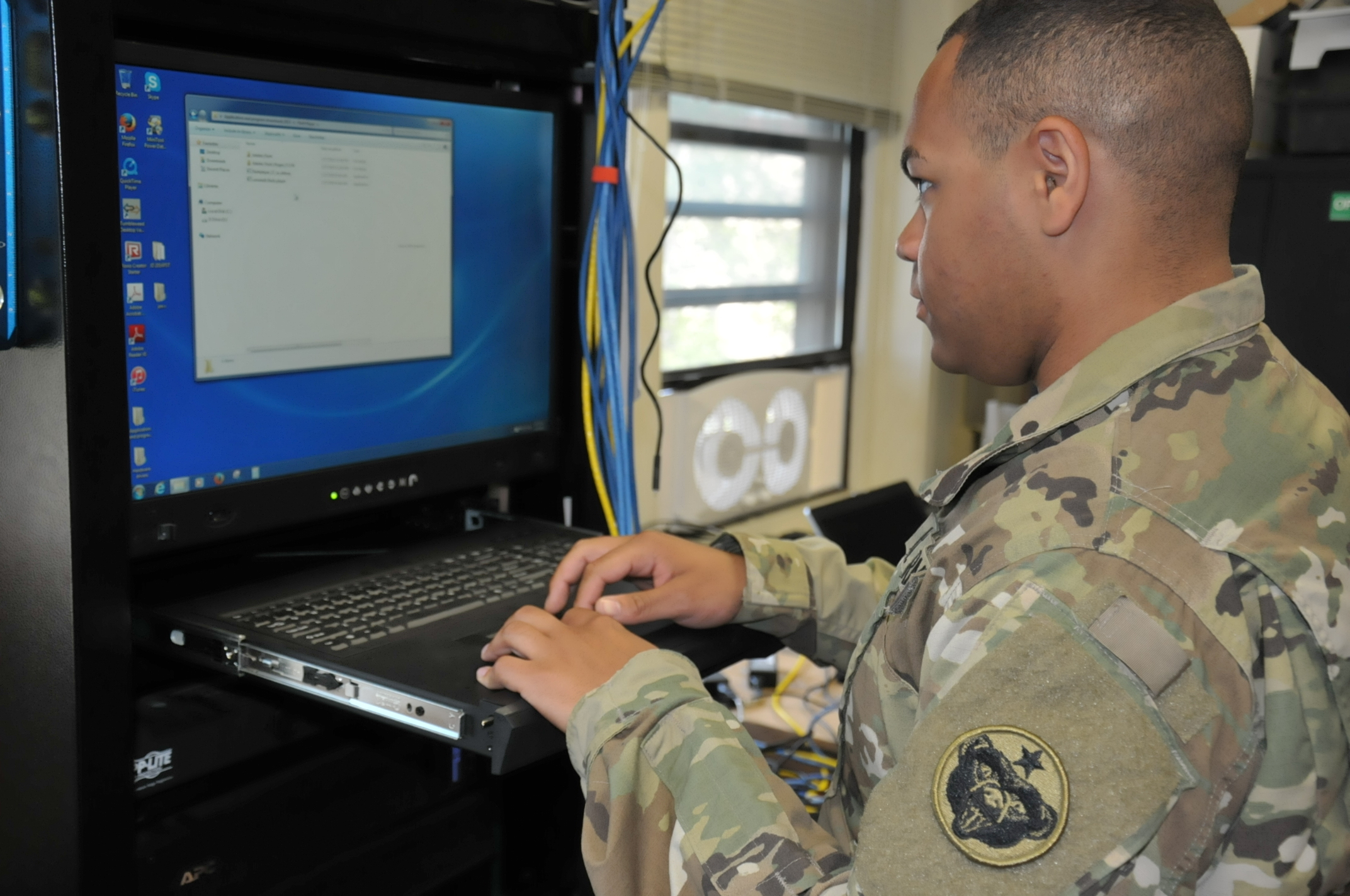 Spc. Isaiah Anderson, an Information Management Officer with U.S. Army Alaska updates the anti-virus software on a stand-alone, off-network computer in the signals section of USARAK headquarters.
