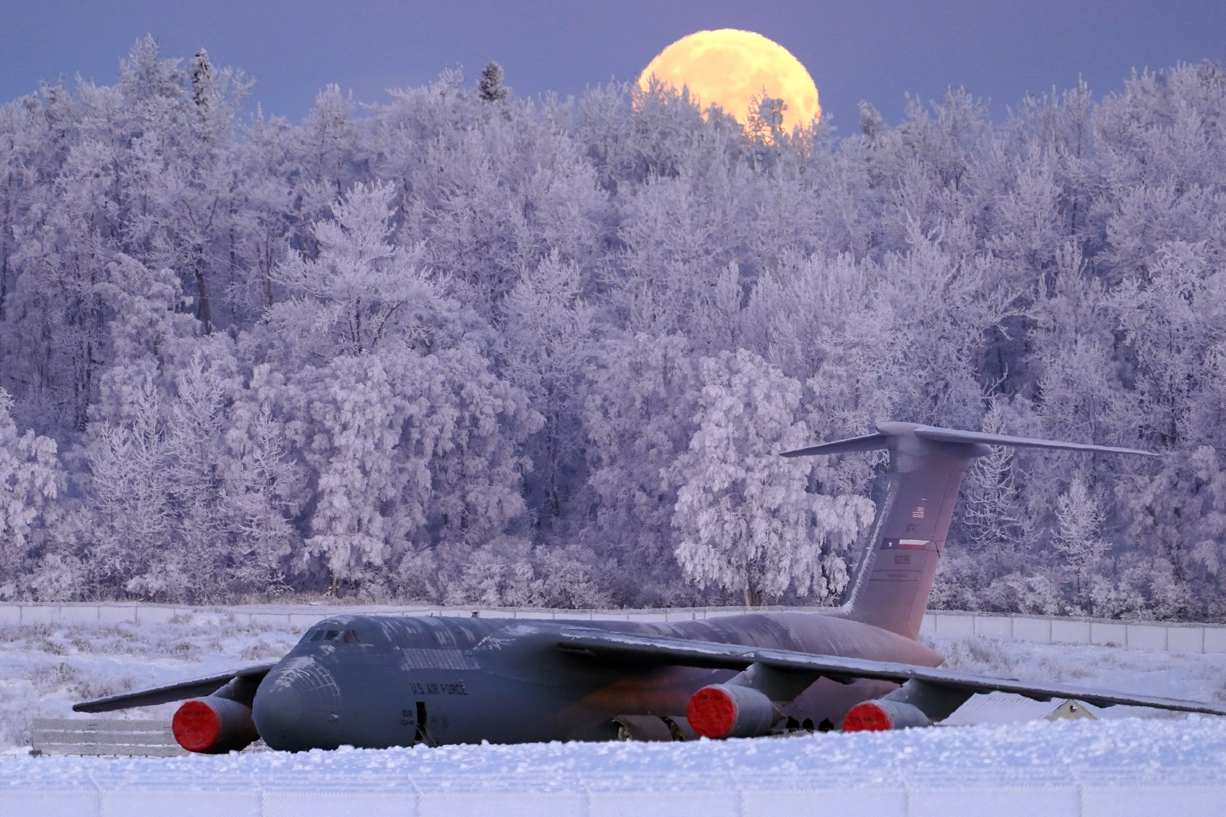 The waning gibbous moon is seen above a U.S. Air Force C-5 Galaxy transport aircraft on the flight line at Joint Base Elmendorf-Richardson, Alaska, Jan 10, 2020, as hoarfrost engulfs nearby trees in -16F weather while airmen work around the plane. (Justin Connaher/Air Force)