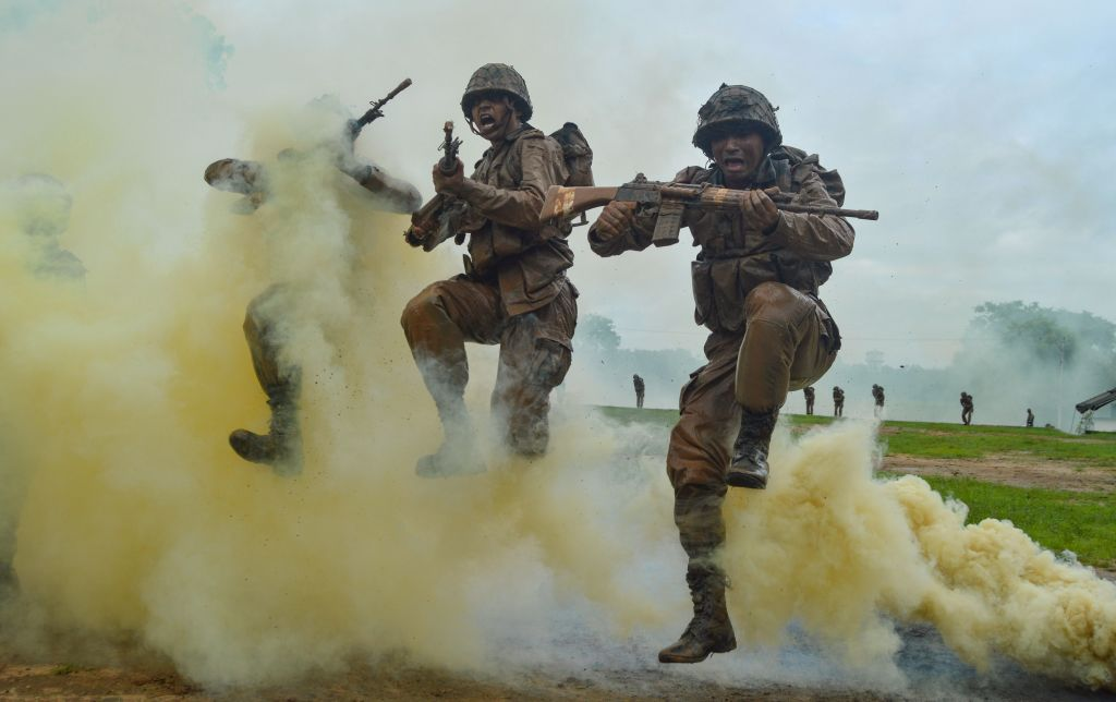 Indian Army recruits shout and jump next to colourful smoke during a training demonstration at the Jak Rifles regimental centre in Jabalpur in Madhya Pradesh state on August 9, 2019. (UMA SHANKAR MISHRA/AFP/Getty Images)
