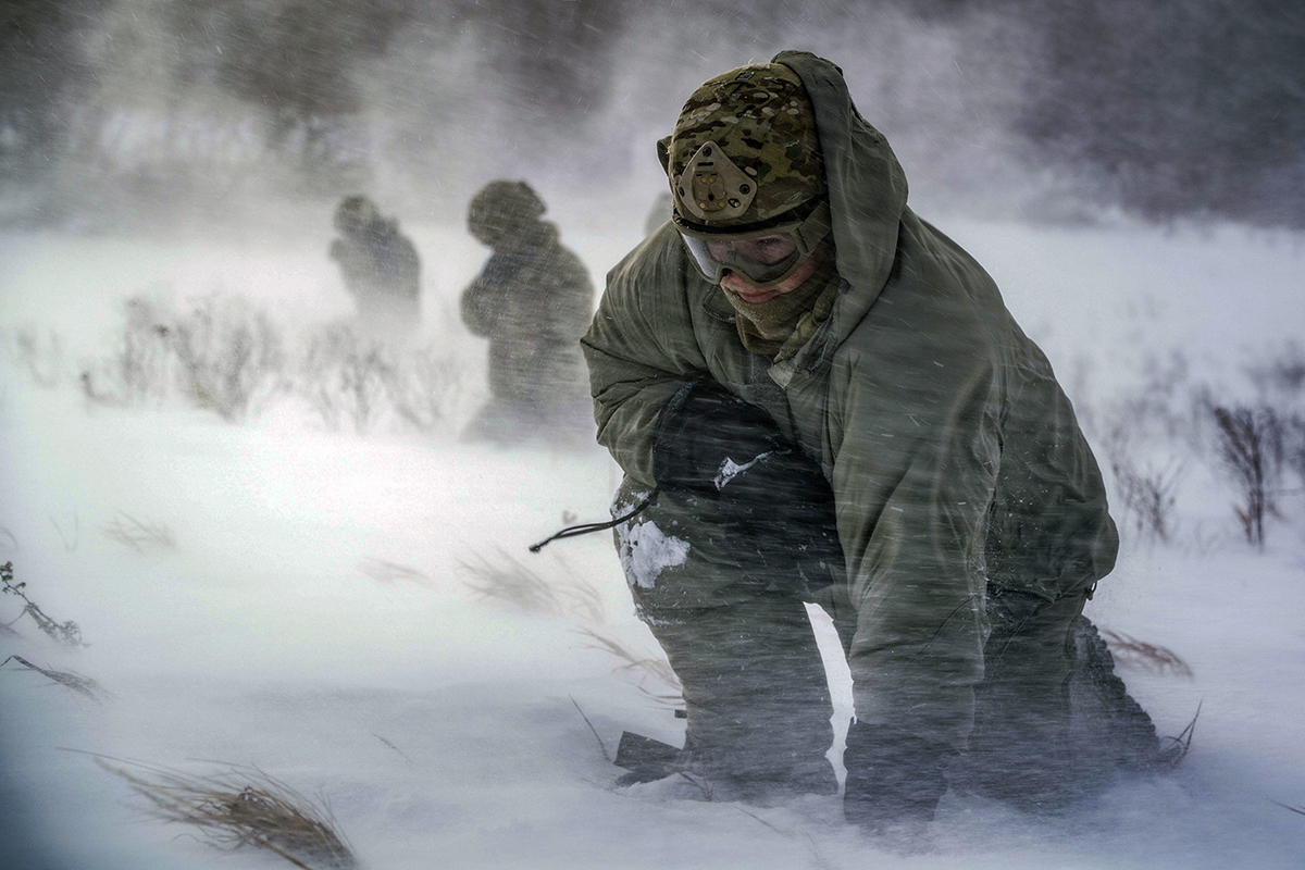 Staff Sgt. Benjamin Reynolds, 891st Missile Security Forces Squadron response force leader, crouches in rotor wash during a field training exercise at Turtle Mountain State Forest, N.D., Feb. 14, 2018. During the exercise 91st Security Forces Group defenders coordinated simulated medical evacuations with two 54th Helicopter Squadron UH-1N Iroquois. (Sr. Airman J.T. Armstrong/Air Force)