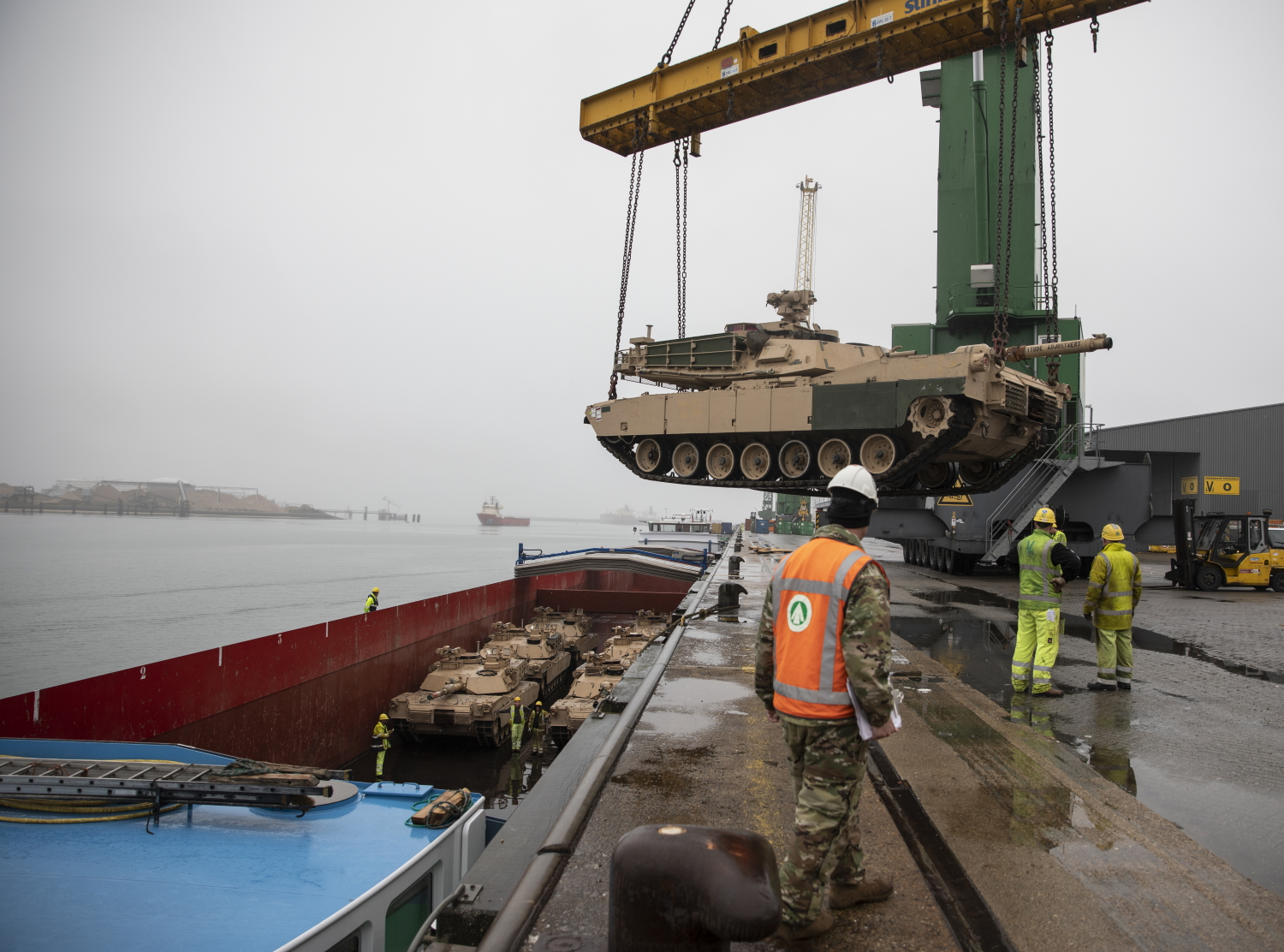 Army Reserve Cpl. Dustin Jobe supervises as an M1A2 Abram Tank is raised over the pier ledge at the Port of Vlissingen, Netherlands, on Oct. 12, 2019. (Sgt. Kyle Larsen/Army)