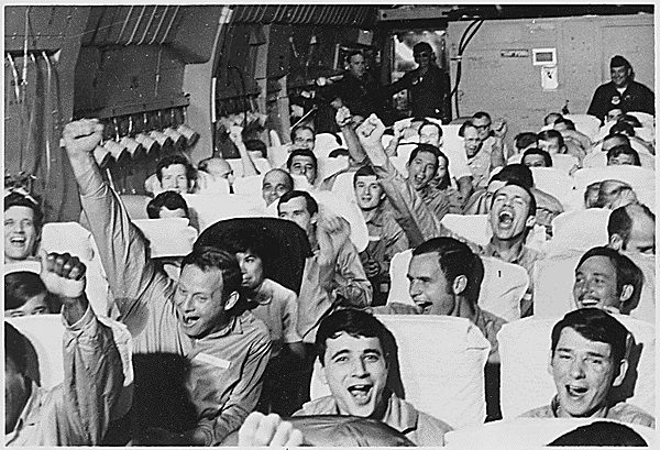American servicemen, all former prisoners of war, cheer as their plane takes off for home from an airfield near Hanoi on Feb. 12, 1973. In all, 591 POWs were released after the Paris Peace Agreement was signed. (National Archives/Marine Corps)