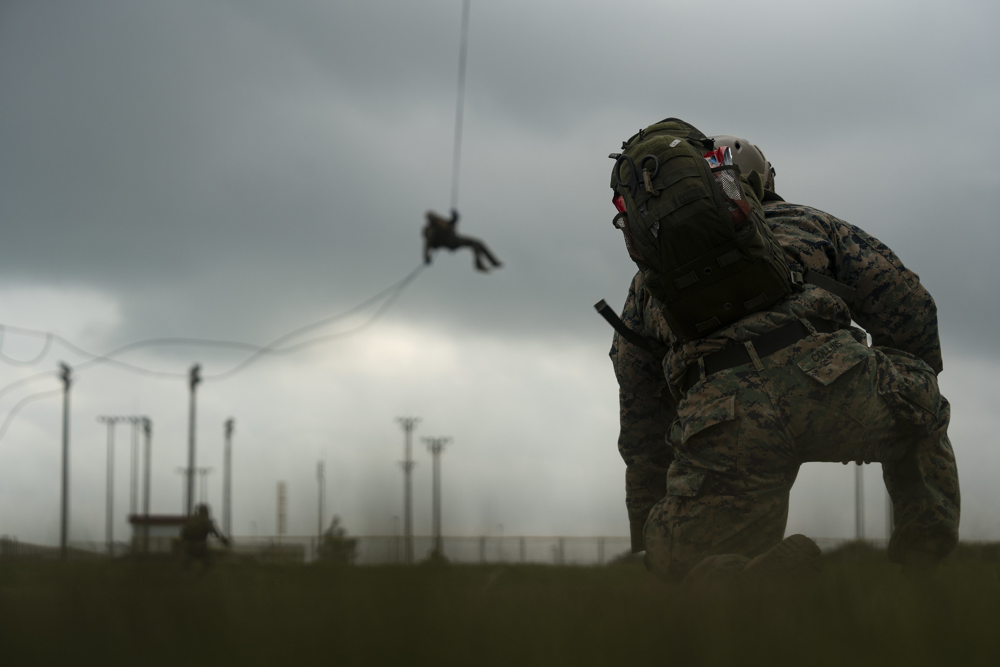 A U.S. Navy corpsman with Expeditionary Operations Training Group, III Marine Expeditionary Force Information Group, supervises students performing helicopter rope suspension technique training at the parade deck on Camp Hansen, Okinawa, Japan, Aug. 14, 2019. (Lance Cpl. Andrew R. Bray/Marine Corps)