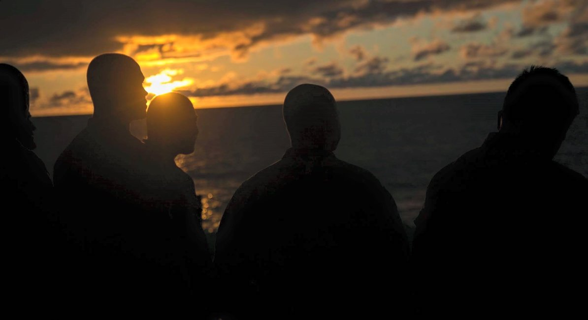 Personnel look out from the amphibious assault ship Essex. A Marine who was reported missing after going overboard from the Essex has been identified and declared deceased. (13th Marine Expeditionary Unit)