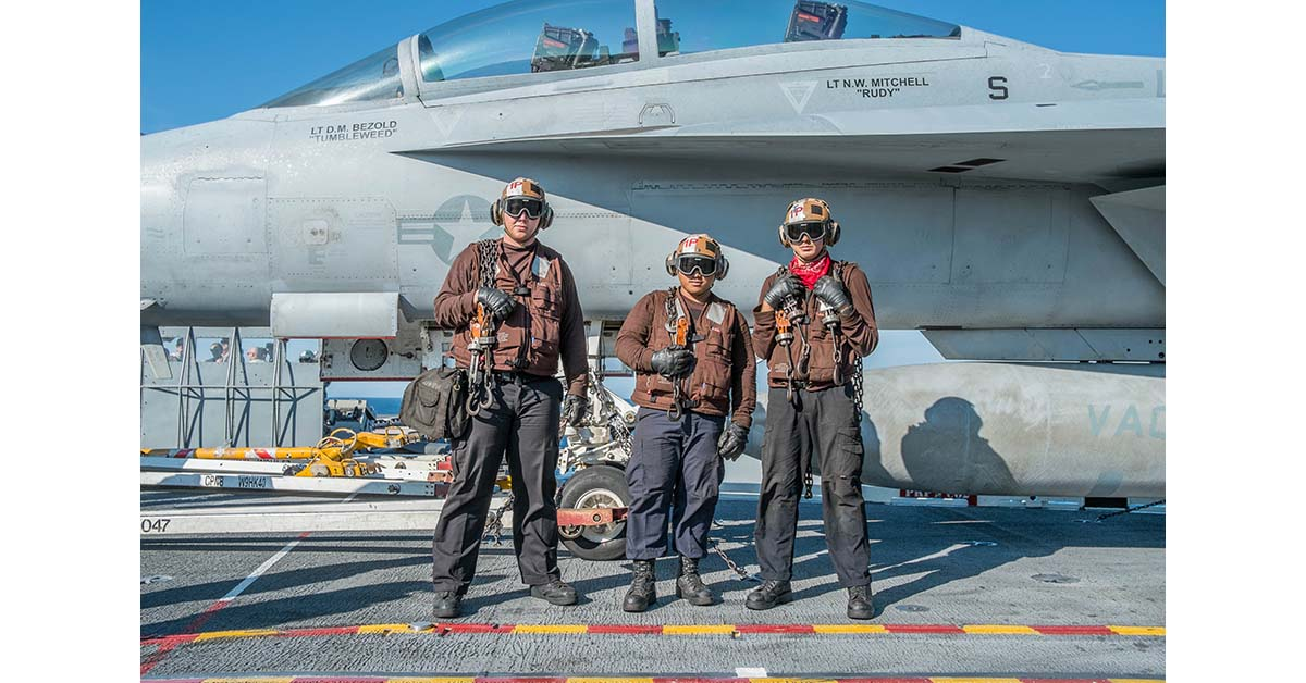 Draped in tie-down chains, U.S. Navy plane captains from Strike Fighter Squadron 31's Tomcatters await the return of F/A-10 Hornets during joint U.S. and French carrier flight operations May 10. (Mark D. Faram/Staff)