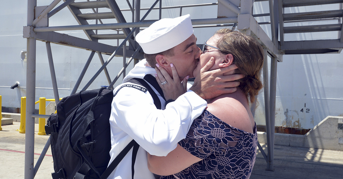 Hospital Corpsman Brett Parrish embraces his wife Alyssa Parrish for the traditional