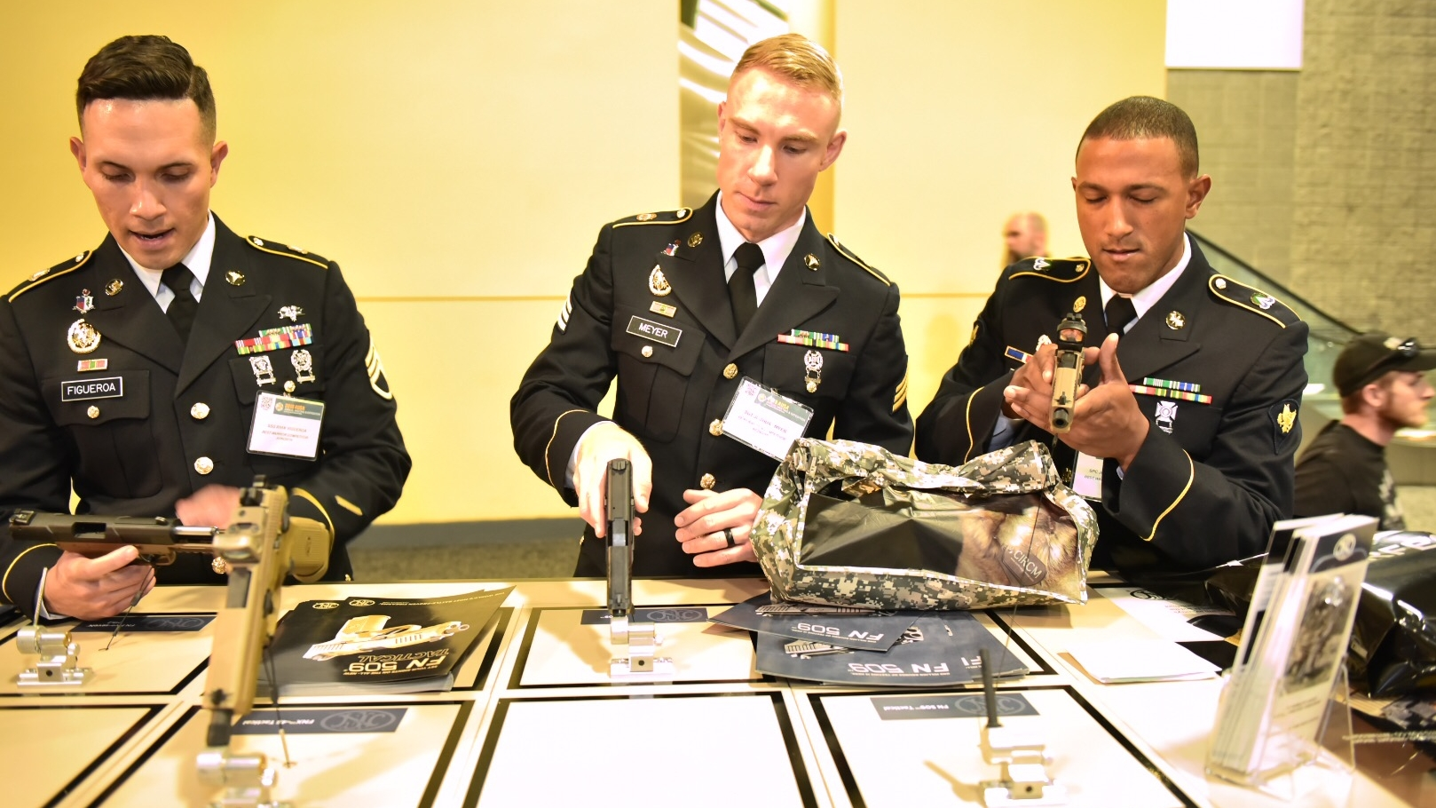 Best warrior competitors Sgt. Joshua Myer SPC Joseph Vazquez, and Staff Sgt. Ryan Figueroa check out FN 509 handguns on display at the 2018 AUSA annual meeting and exposition in Washington, DC. (Stephen Barrett/Special to Defense News & Army Times)