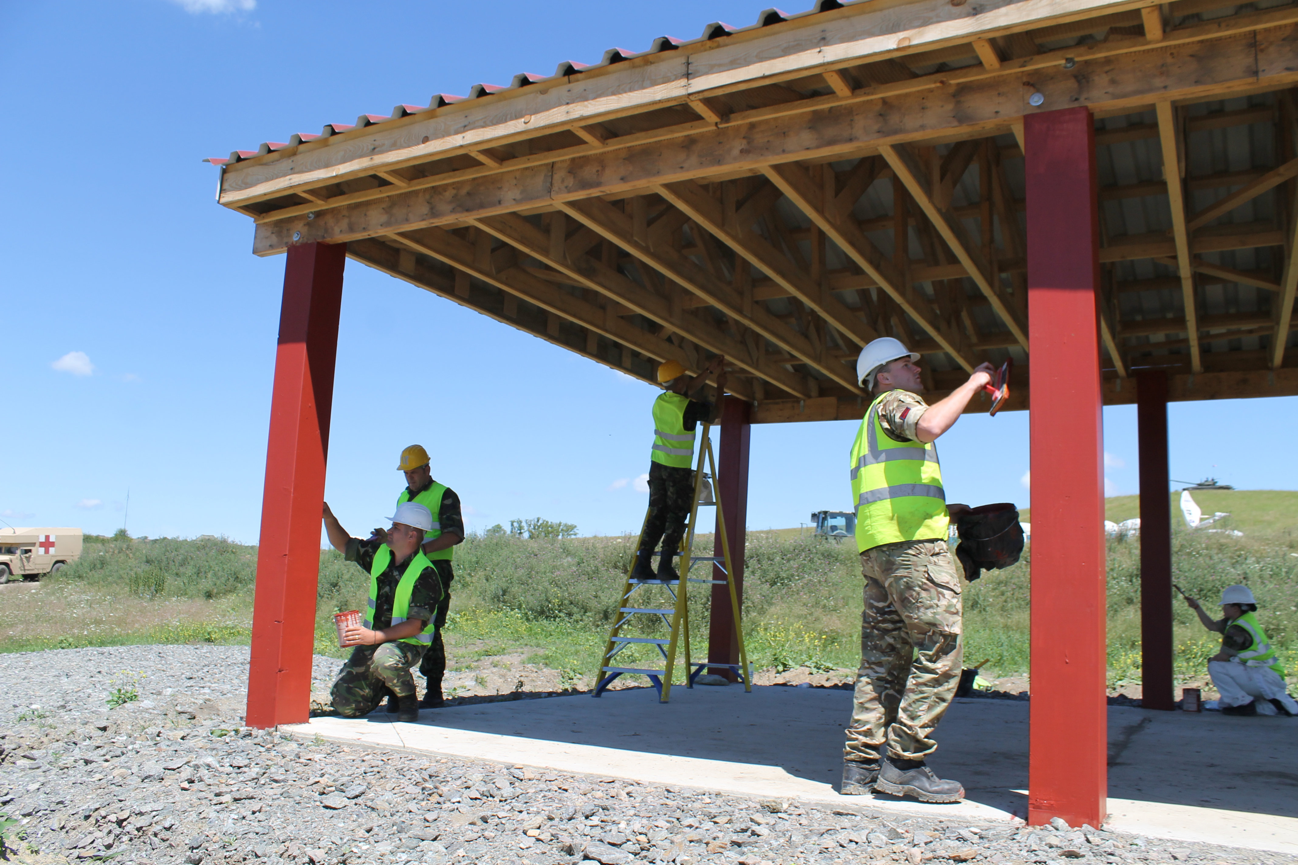Romanian soldiers put finishing touches on the multipurpose shelter to service the ammunition storage facility and the nonstandard live fire range as Lt. Gen. Ben Hodges and U.S. ambassador to Romania Hans Klemm toured the work performed during Resolute Castle, the exercise for engineers training to build infrastructure, at the Joint National Training Center in Cincu, Romania. (Jen Judson/Staff)