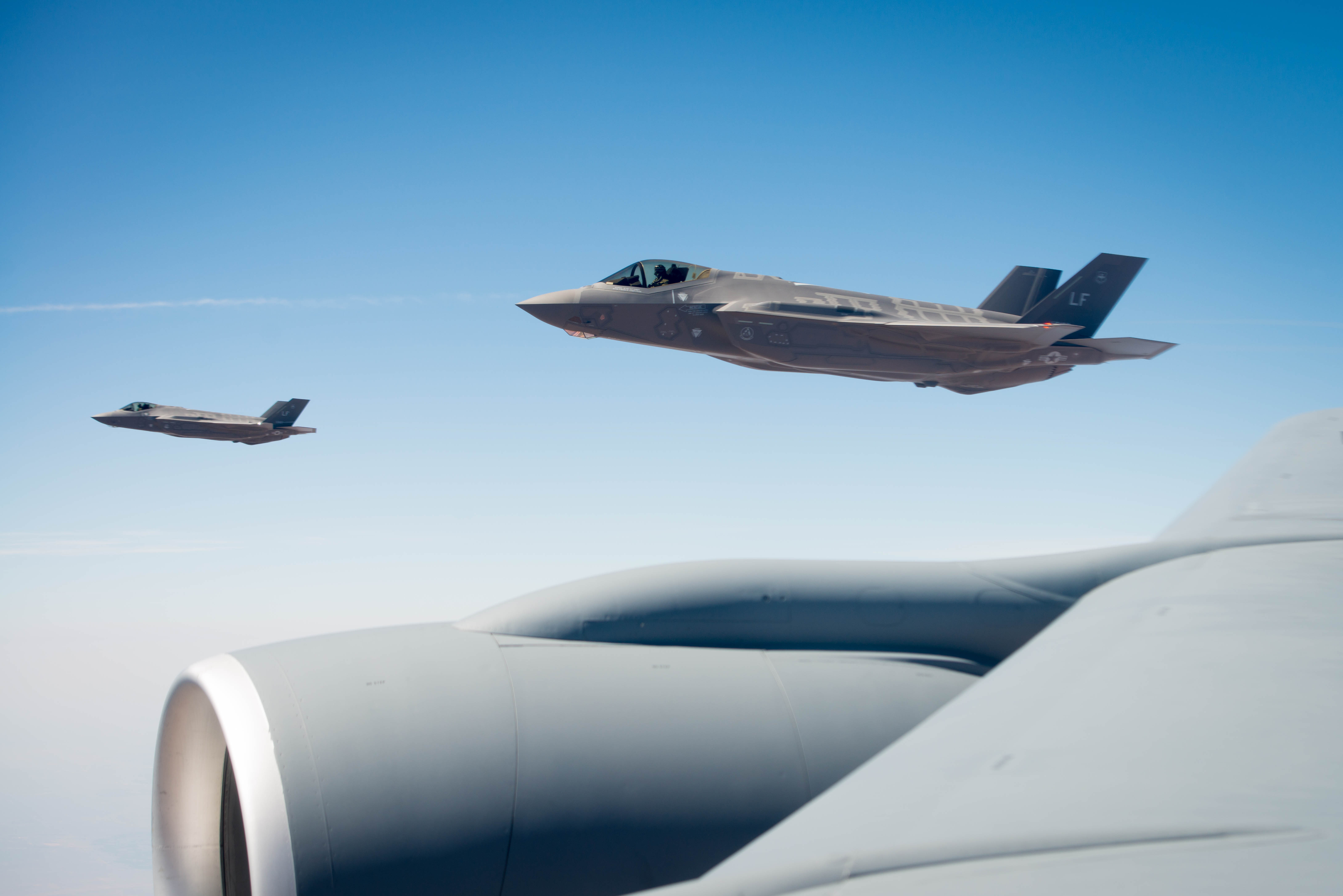 Two F-35A Lighting IIs assigned to the 62nd Fighter Squadron, Luke Air Force Base Ariz, fly near an Arizona National Guard KC-135 Stratotanker Aug. 4, 2017. Four F-35's participated in a missing man formation fly-over during 2nd Lt. Charles E. Carlson's funeral in Pennsylvania more than 70 years after being shot down over Germany in World War II when he was assigned to the 62nd FS. (Staff Sgt. Jensen Stidham/Air Force)
