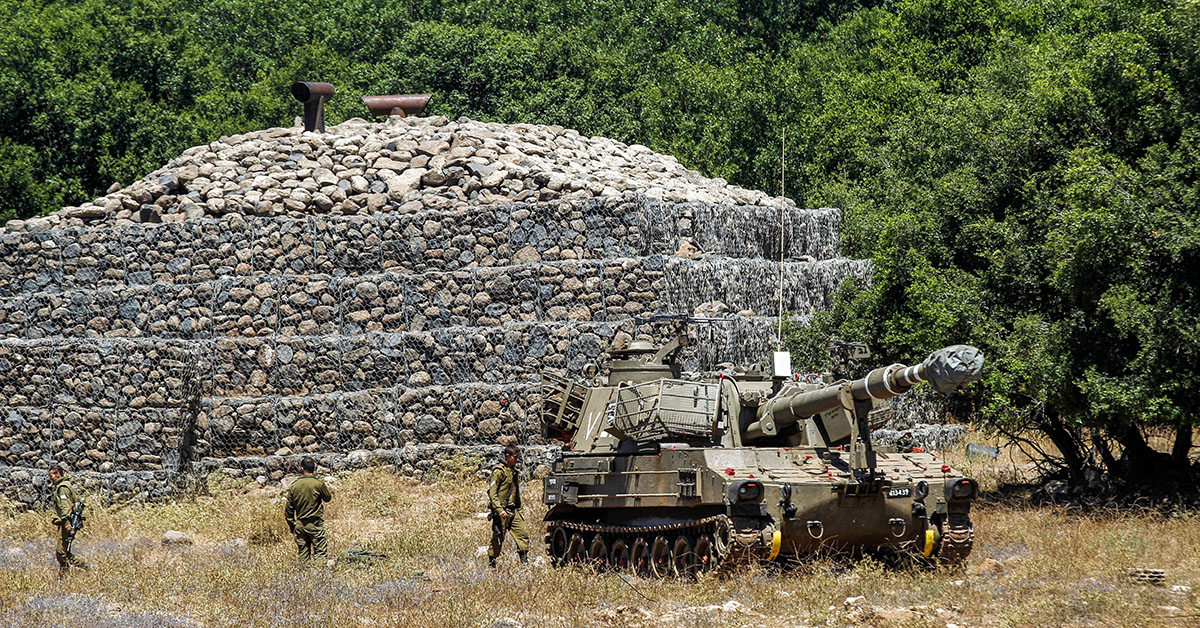 Israeli soldiers walk past a bunker with a mobile artillery piece seen deployed near the border with Syria in the Israeli-annexed Golan Heights on July 1, 2018. (Jalaa Marey/AFP via Getty Images)