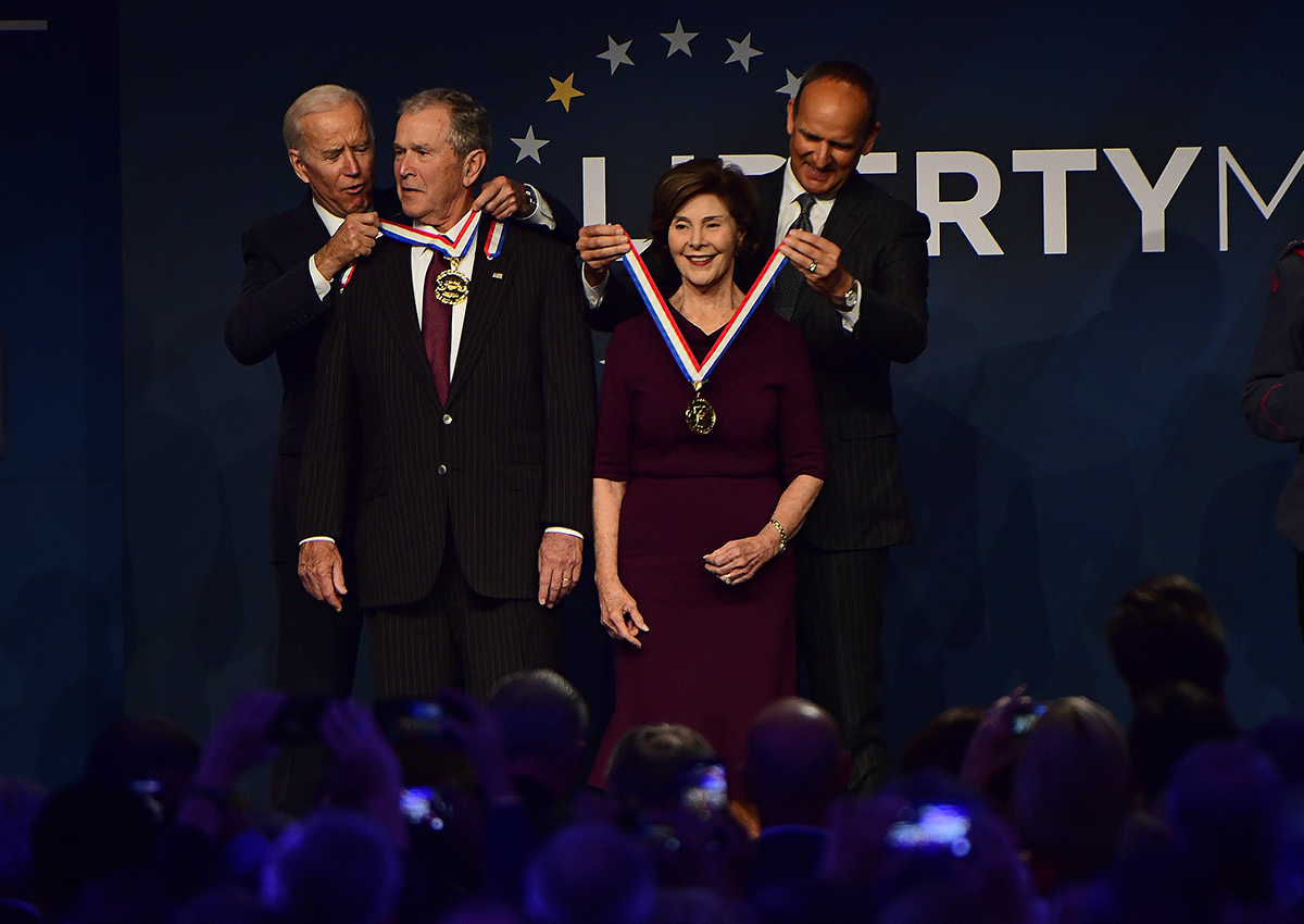 Former U.S. Vice President Joe Biden, from left, bestows a medal on former U.S. President George Bush as former first lady Laura Bush has the same bestowed by Doug DeVos, executive committee chairman for the National Constitution Center, at the National Constitution Center, Sunday, Nov. 11, 2018 in Philadelphia. Both received the 30th annual Liberty Medal, an honor given to those who are committed to freedom and human rights globally. (Corey Perrine/AP)