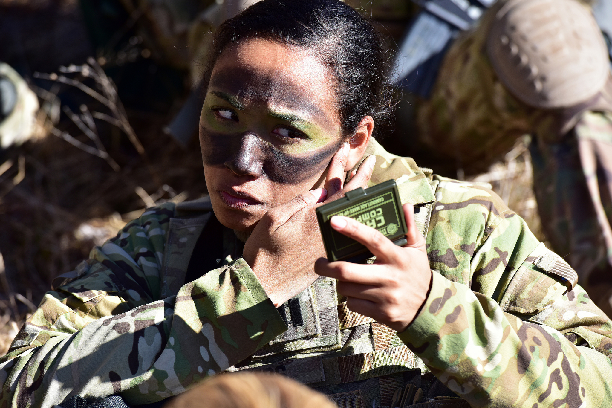 Capt. Julissa Myers puts the finishing touches to her face paint camouflage in preparation a blank-fire exercise as part of Lipizzaner V at Pocek Range in Postonja, Slovenia, March 12, 2019. (Paolo Bovo/Army)