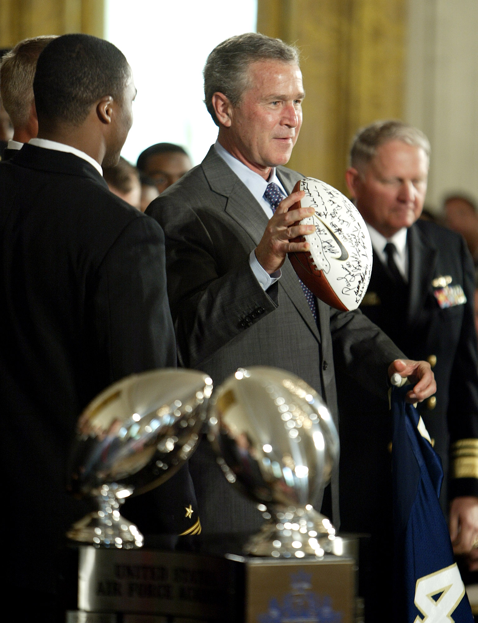 President Bush acts like he is going to throw a football given to him by team members as he participates, Monday, April 19, 2004, in a presentation of the Commander-in-Chief's Trophy to the United States Naval Academy football team in the East Room of the White House. Other are indentified. (AP Photo/Ron Edmonds)