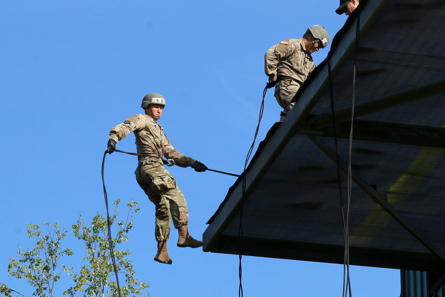 A soldier attending Air Assault School jumps from a 58-foot tower for the first time as he rappels down a rope at Joint Base Elmendorf-Richardson, July 16, 2018. (Sgt. Alex Skripnichuk/Army)