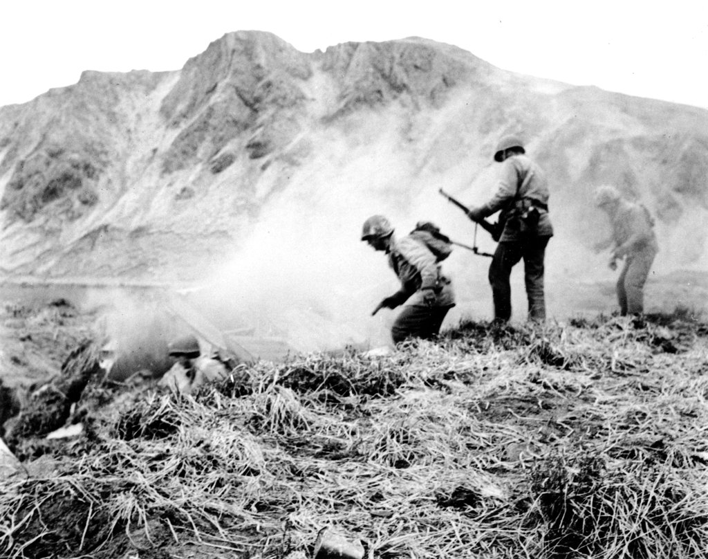 In this June 1943 file photo, a U.S. squad armed with guns and hand grenades close in on Japanese holdouts entrenched in dugouts during World War II on Attu Island, part of the Aleutian Islands of Alaska. May 30, 2018 will mark the 75th anniversary of American forces recapturing Attu Island in Alaska's Aleutian chain from Japanese forces. It was the only World War II battle fought on North American soil. (AP)