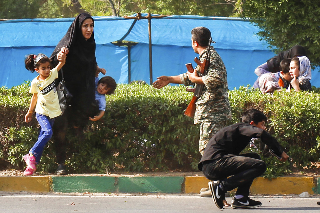A woman rushes her children to shelter as a soldier tries to help them, during a shooting at a military parade marking the 38th anniversary of Iraq's 1980 invasion of Iran, in the southwestern city of Ahvaz, Iran. Gunmen on Saturday attacked the military parade, killing several and wounding others, state media said. (Fatemeh Rahimavian/Fars News Agency via AP)