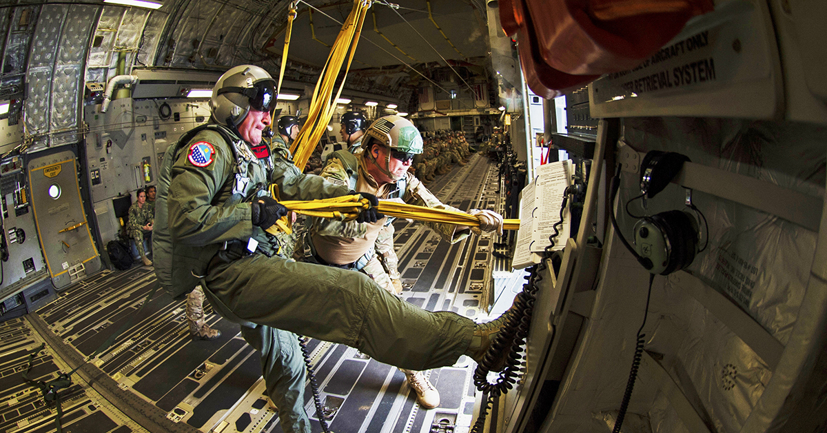 Air Force aircrew, assigned to the 15th Support Squadron, pull in the static lines after all jumpers have exited the aircraft during static line airborne training operations as part of during the Rim of the Pacific (RIMPAC) exercise. (MC Cynthia Z. De Leon/Released)