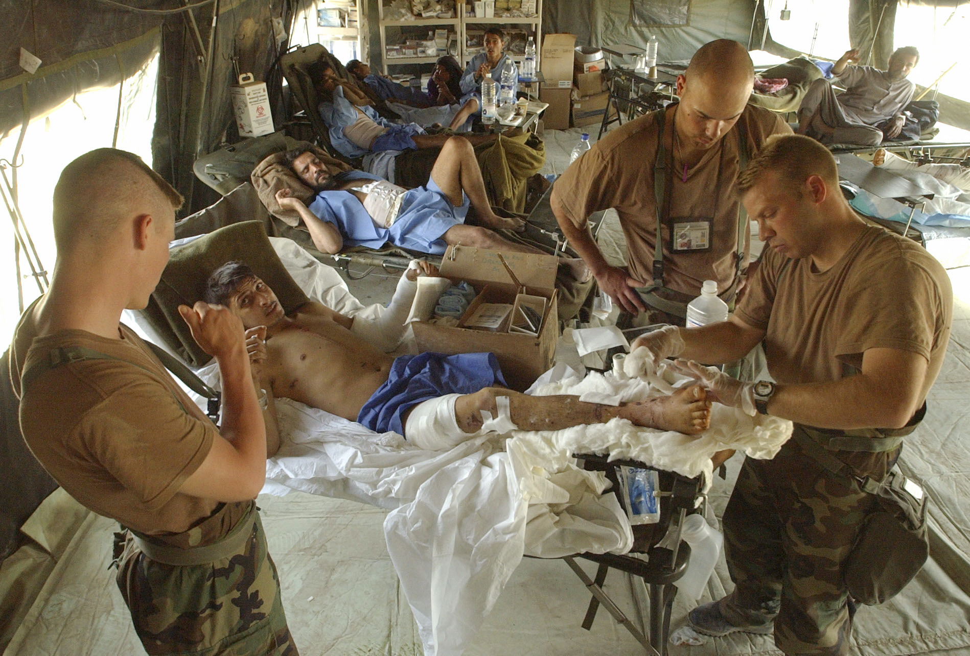 Medical personel of the U.S. Army 86th Combat Support Hospital located at Tallil air base in Southern Iraq, change the dressings on a wounded Iraqi civilian. Spec. Brian Herndon,left, from Carlsbad, NM, 1st Lt. Dave Allen, middle right, from Columbus OH, and Spec. James Shead, right, from Austin Texas care for the wounded. (Alan Lessig/Army Times)