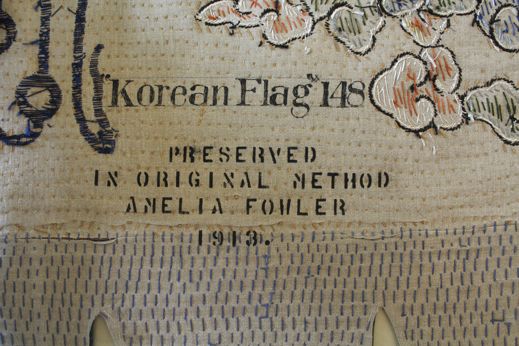This undated photo provided by the U.S. Naval Academy Museum shows a detail of a flag, showing Amelia Fowler's stamp at the U.S. Naval Academy Museum in Annapolis, Md. Fowler, a well-known flag preserver who restored the original Star-Spangled Banner in 1914, was contracted in 1912 to conserve the academy's collection of trophy flags. She worked with dozens of other women in the museum's Mahan Hall, using a patented stitching pattern to help preserve fabric. (United States Naval Academy Museum via AP)