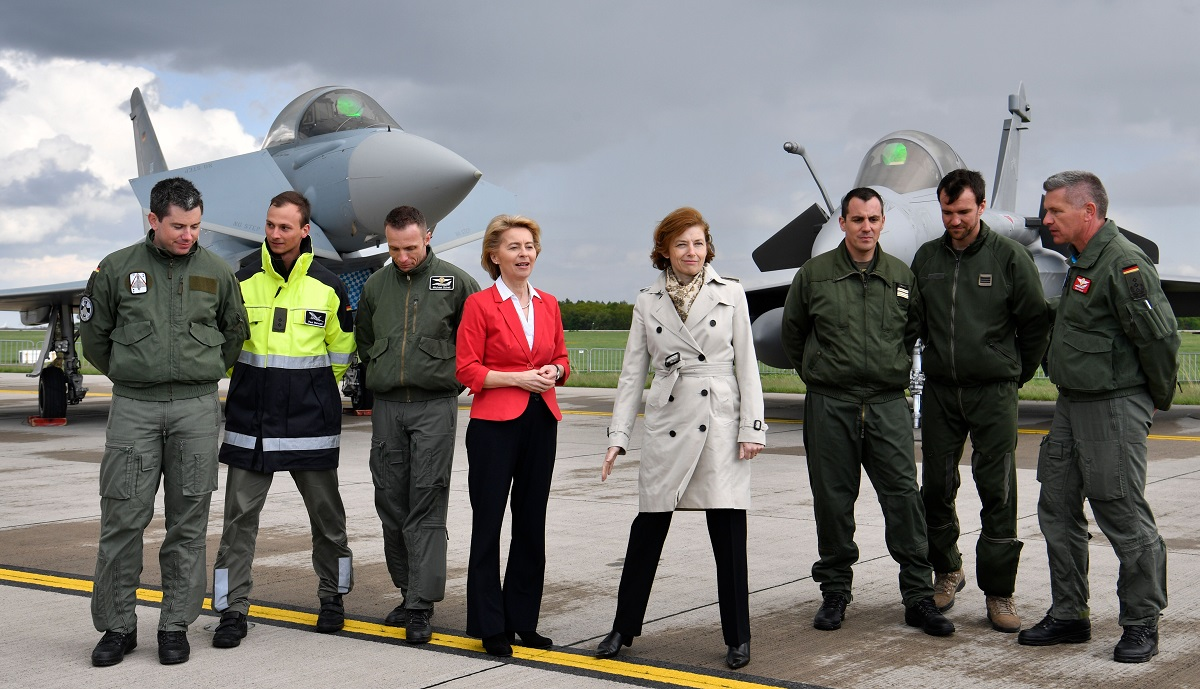 German Defence Minister Ursula von der Leyen, center left, and her French counterpart Florence Parly, center right, pose with pilots in front of a Eurofighter Typhoon, left, nd a Dassault Rafale (John MacDougall/AFP via Getty Images)