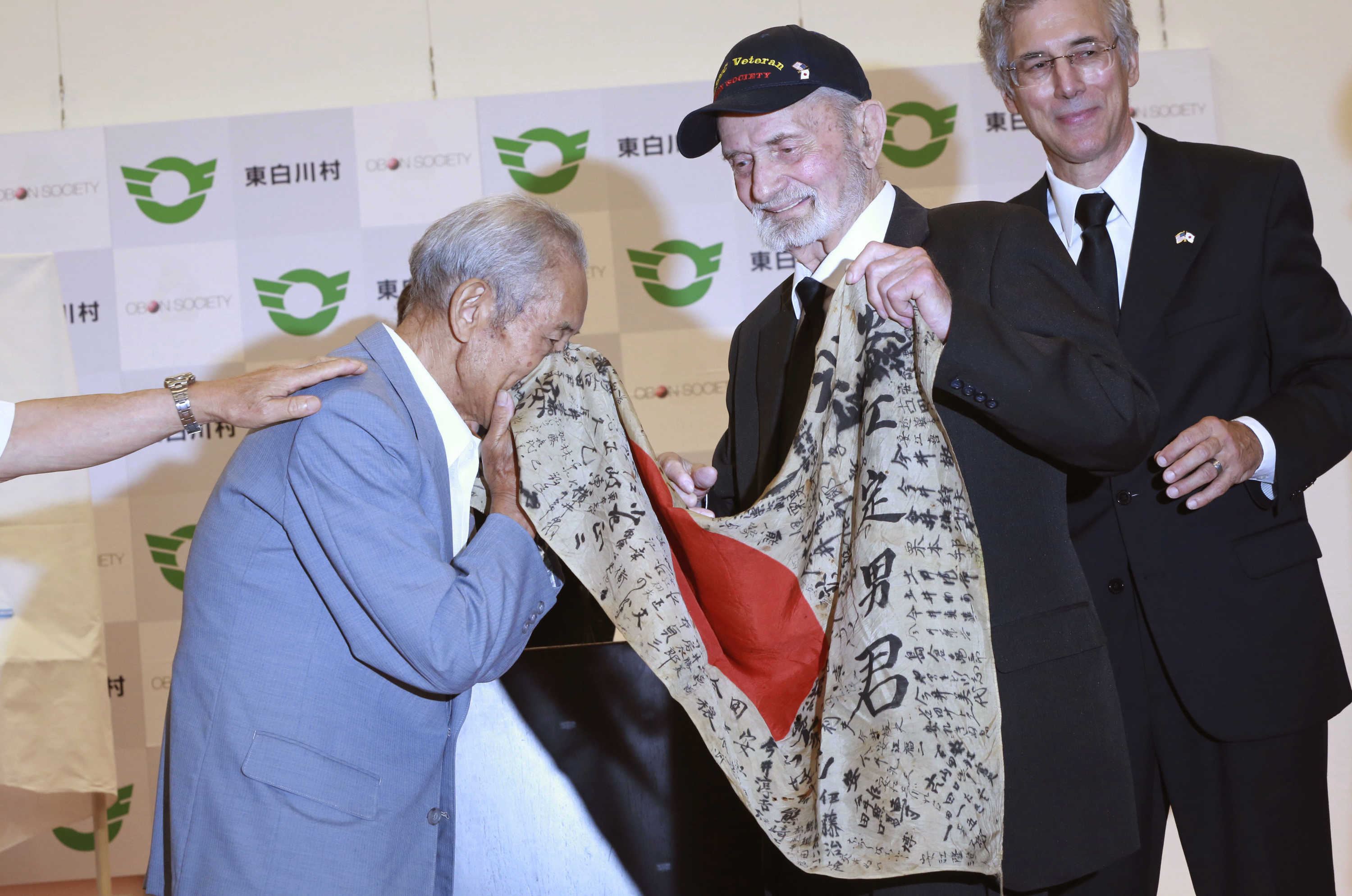 WWII veteran Marvin Strombo, center, returns to Tatsuya Yasue, left, a Japanese flag with autographed messages which was owned by his brother Sadao Yasue, who was killed in the Pacific during World Work II, during a ceremony in Higashishirakawa, in central Japan's Gifu prefecture Tuesday, Aug. 15, 2017. (Eugene Hoshiko/AP)