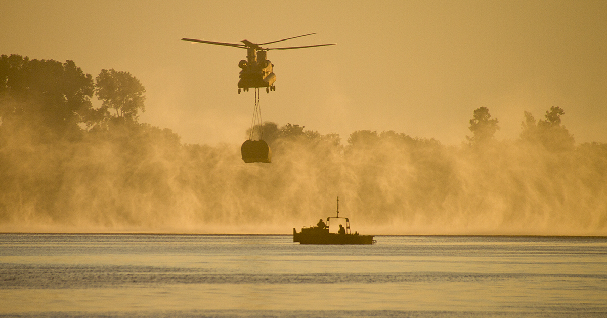 A CH-47 Chinook airdrops an interior bridge bay during River Assault 2018 on the Arkansas River near Fort Smith, Ark., July 25, 2018. The annual exercise brought together Marine Corps and Army units for one of the largest Army Reserve engineer exercises in the country. (Sgt. 1st Class Scott Raymond/KY National Guard)