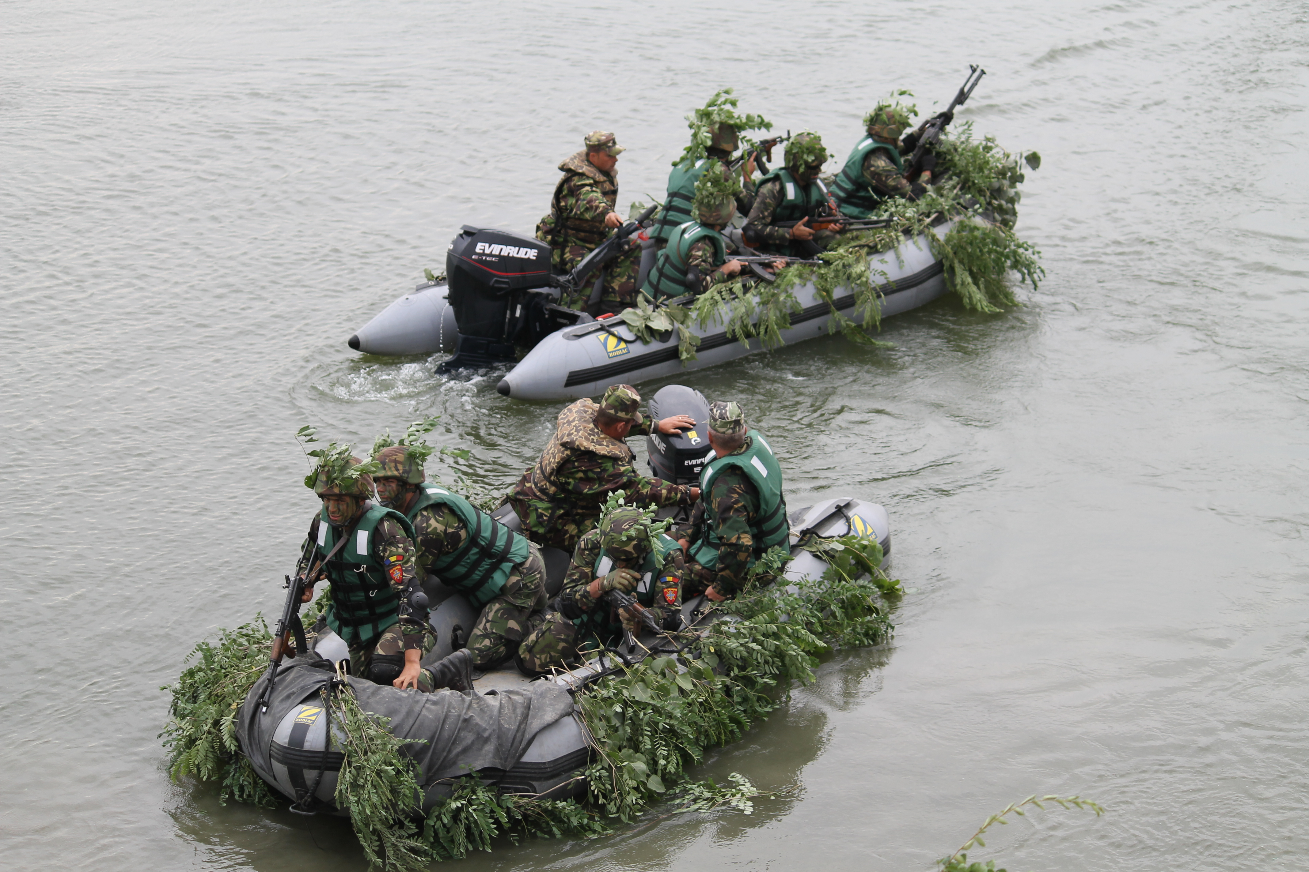 Well-camouflaged Romanian troops load into high-speed rafts within seconds on the side of the Danube and begin the short journey across to support friendly forces on the other shoreline, fending off enemy advances. (Jen Judson/Staff)