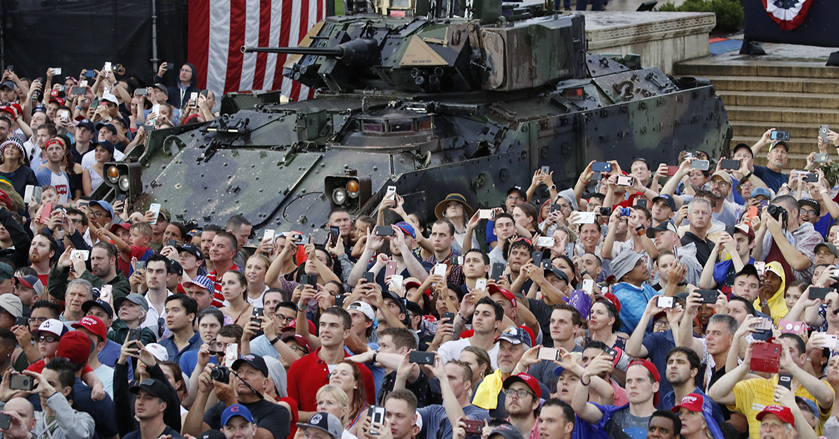 Audience members photograph a flyover in front of a Bradley Fighting Vehicle as President Donald Trump speaks during an Independence Day celebration in front of the Lincoln Memorial, Thursday, July 4, 2019, in Washington. (AP Photo/Alex Brandon)