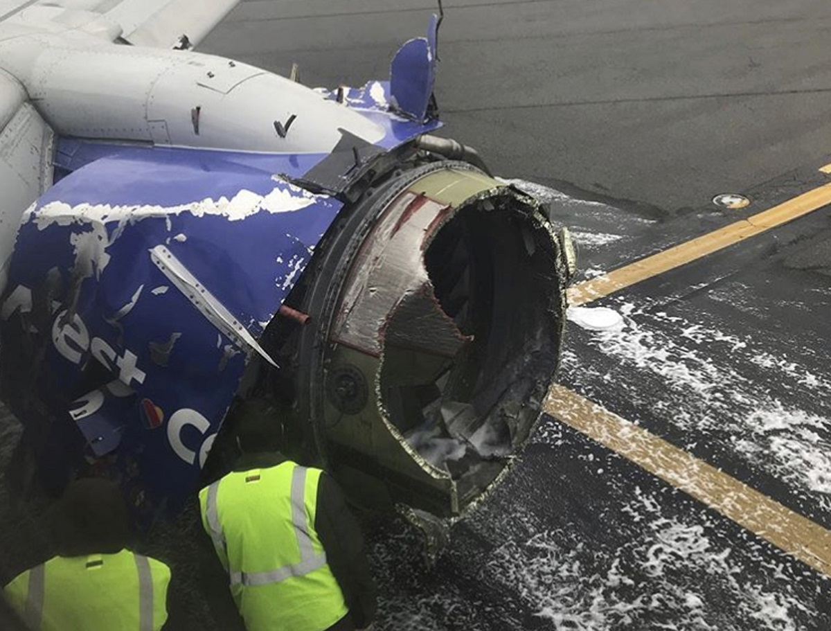 The engine on a Southwest Airlines plane is inspected as it sits on the runway at the Philadelphia International Airport after it made an emergency landing in Philadelphia on April 17. On Thursday, an Arizona congresswoman introduced a resolution to honor the pilot — the first woman ever to pilot F/A-18 Hornets — for safely landing the plane. (Amanda Bourman/AP)