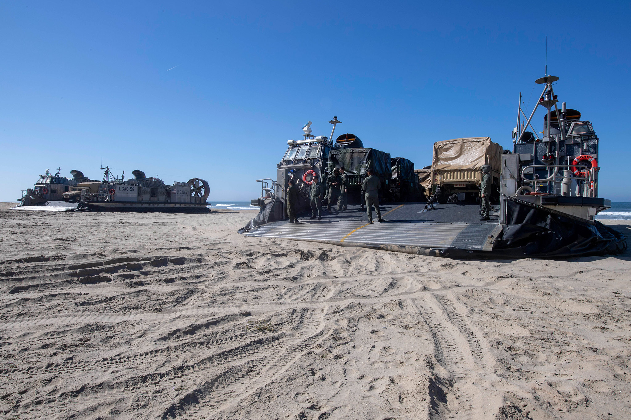 Landing craft air cushions prepare to unload vehicles and Marines on March 30, 2019, in the Indo-Pacific area of operations. (Mass Communication Specialist 2nd Class Kyle Carlstrom/Navy)