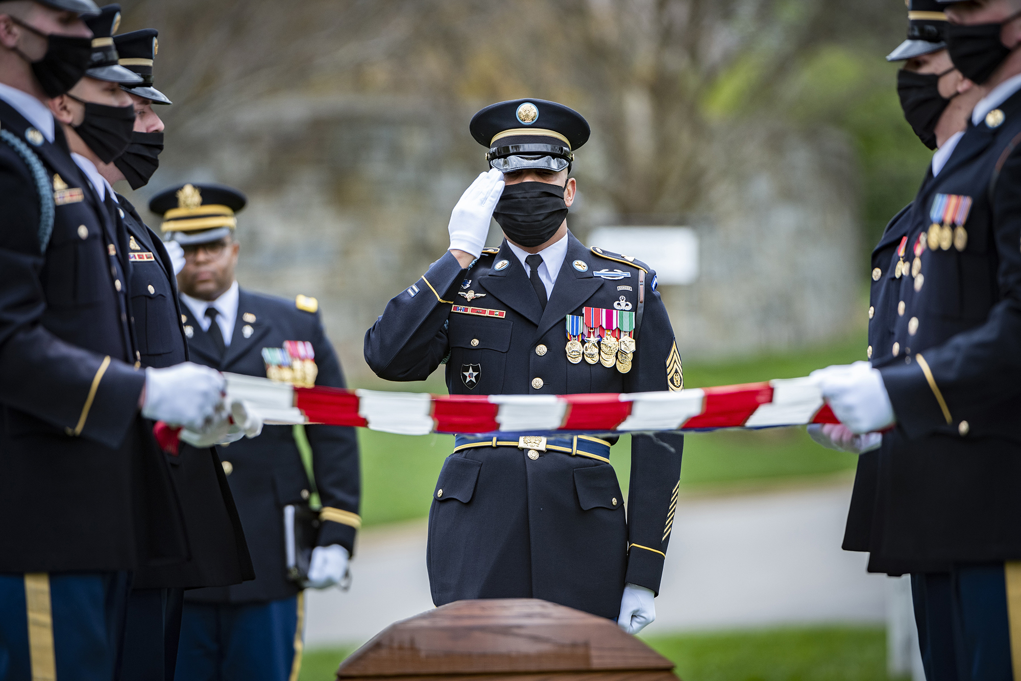 A soldier assigned to The Old Guard renders honors shortly after the chaplain provided his blessing April 14, 2020, during the funeral for retired Army Command Sgt. Maj. Robert M. Belch in Arlington National Cemetery, Arlington, Va. Given current health protection guidance from the secretary of defense, Old Guard soldiers wear face coverings to mitigate the spread of COVID-19 while executing the memorial affairs mission. (Elizabeth Fraser/Army)