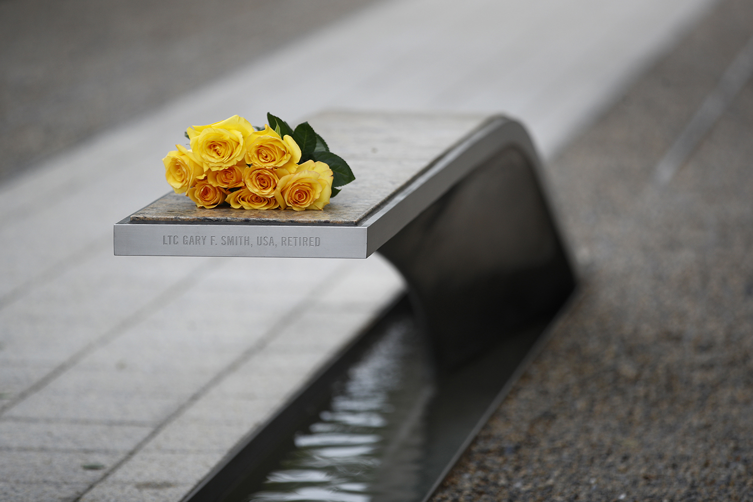 Flowers rest on a bench bearing a name in memory of retired U.S. Army Lt. Col. Gary Smith before a ceremony in observance of the 18th anniversary of the Sept. 11 attacks at the Pentagon in Washington, Wednesday, Sept. 11, 2019. (Patrick Semansky/AP)