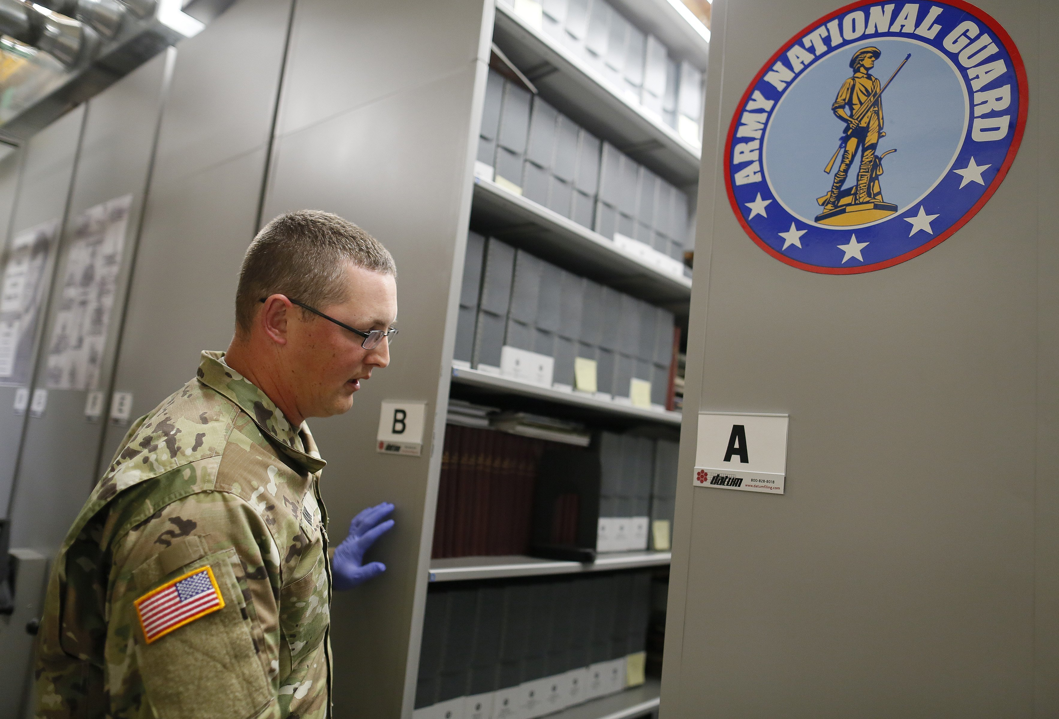 In this July 17, 2018, photo, Sgt. 1st Class Josh Mann, the Ohio Army National Guard historian, opens one of the archival filing cabinets containing historical books and documents inside the Beightler Armory in Columbus, Ohio. The Ohio National Guard is celebrating its 230 years of service. (Adam Cairns/The Columbus Dispatch via AP)