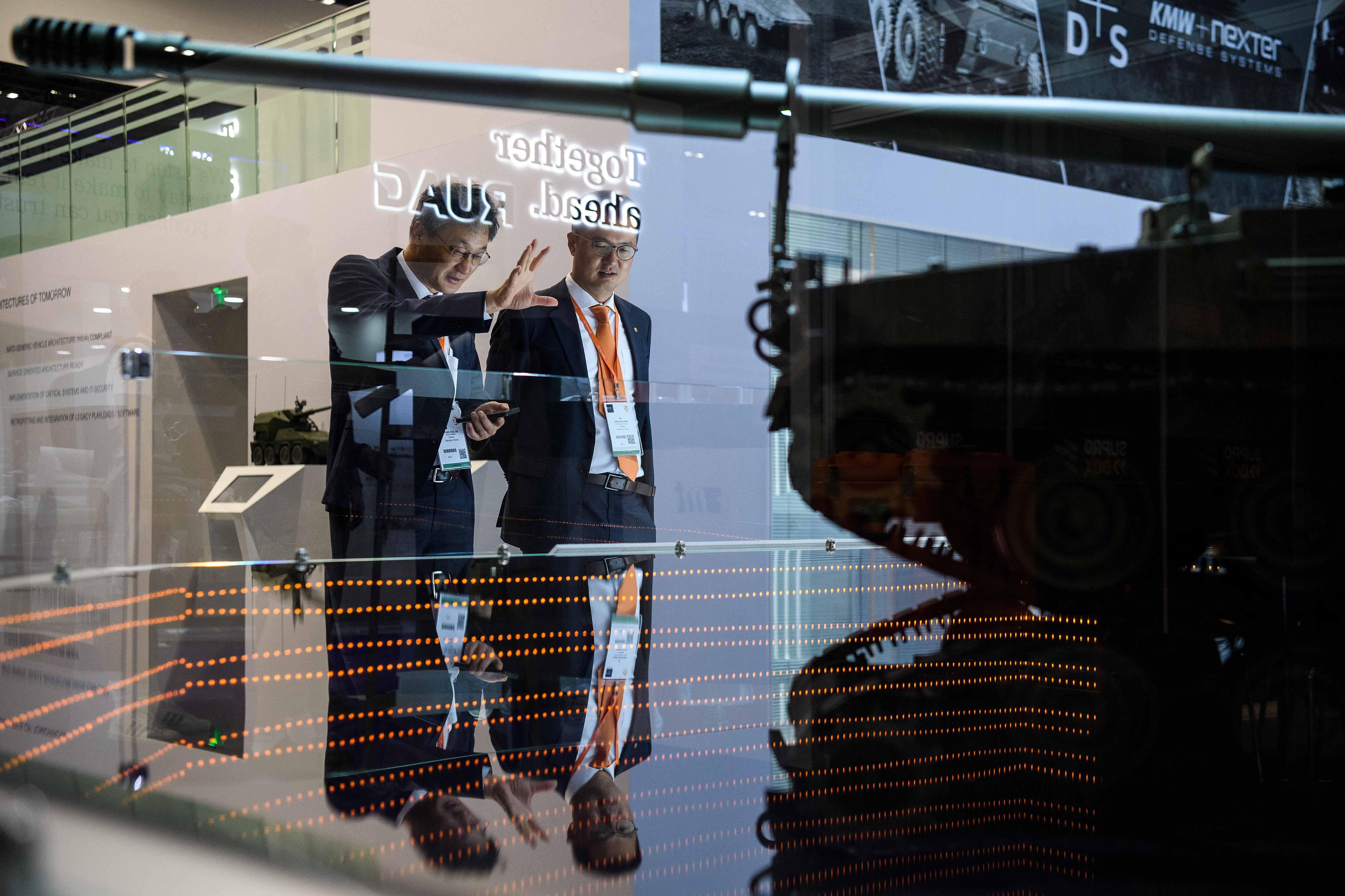 On the second day of the DSEI arms fair, vice president of the Hanwha Group, Byung Chul An, left, looks at a model of the K9 Thunder self-propelled howitzer. (Leon Neal/Getty Images)