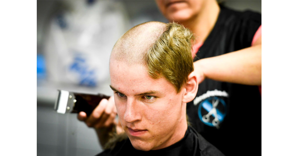 Air Force Academy appointee Grant Schlichting receives a buzzcut from Mary Deardorff, an Air Force barber, as Schlichting and approximately 1,200 members of the Air Force Academy joined as the Class of 2022 began their in-process and Basic Cadet Training, their first introduction to the Academy at the U.S. Air Force Academy on Thursday June 28, 2018, in Colorado Springs, Colo. (Dougal Brownlie/The Gazette via AP)