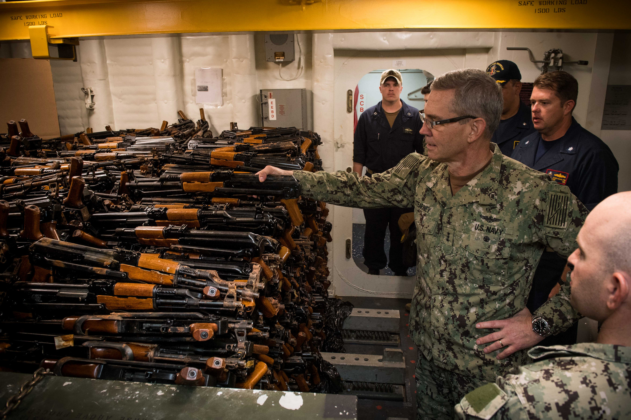 Vice Adm. Scott Stearney, commander of U.S. Naval Forces Central Command, U.S. 5th Fleet and Combined Maritime Forces, looks at a cache of over 2,500 AK-47 automatic rifles seized during maritime security operations aboard the guided-missile destroyer USS Jason Dunham (DDG 109) on Oct. 24, 2018, in Manama, Bahrain. (MC3Jonathan Clay/Navy)