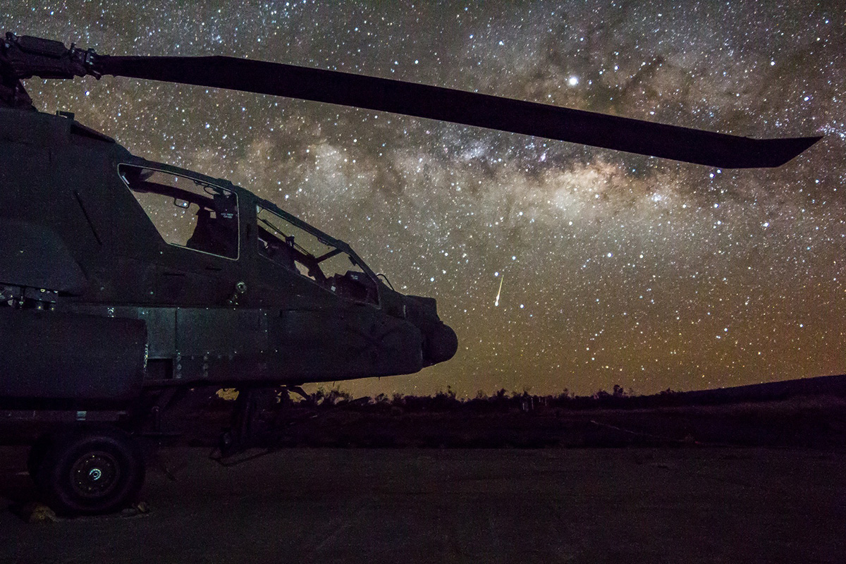 Army AH-64 Apache attack helicopter sits on the flight line April 13, 2019, while a shooting star falls in the sky on FARP 17, Pōhakuloa Training Area, Hawaii. (Capt. Keith Kraker/Army)